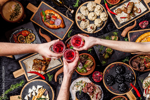 Obraz Georgian cuisine. A large laid table of different dishes for the whole family on a day off. Kebab, Lula, Lavash, Suluguni cheese, Khachipuri, Khinkali. background image, top view - fototapety do salonu