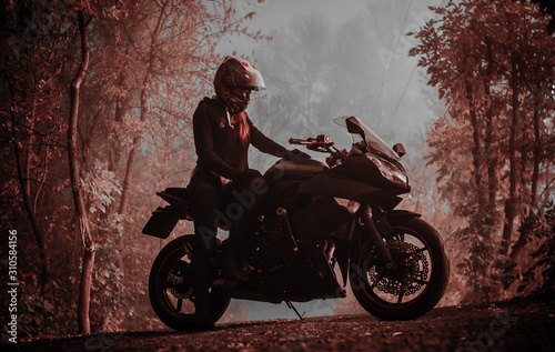 Woman on a motorcycle in the fog in the woods