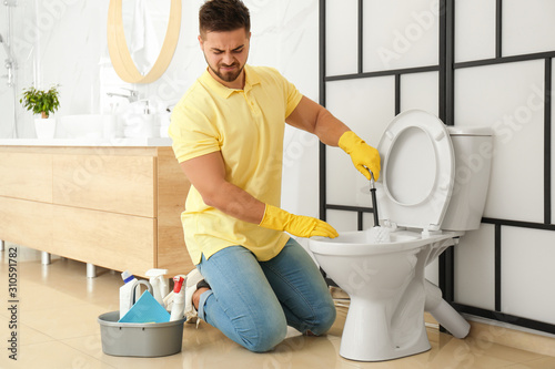Obraz Young man feeling disgust while cleaning toilet bowl in bathroom - fototapety do salonu