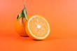closeup of full and half cut fresh juicy orange on orange color backdrop citrus fruits