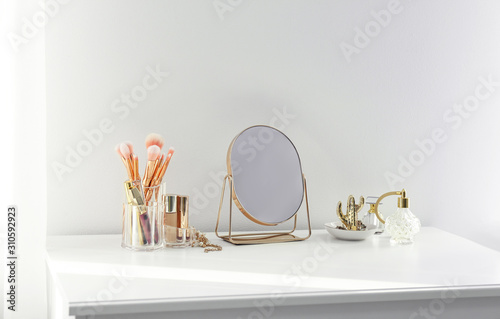 Photo Small mirror and makeup products on white dressing table indoors