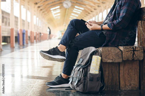 Ταπετσαρία τοιχογραφία Young man traveler sitting with using mobile phone choose where to travel and bag waiting for train at train station