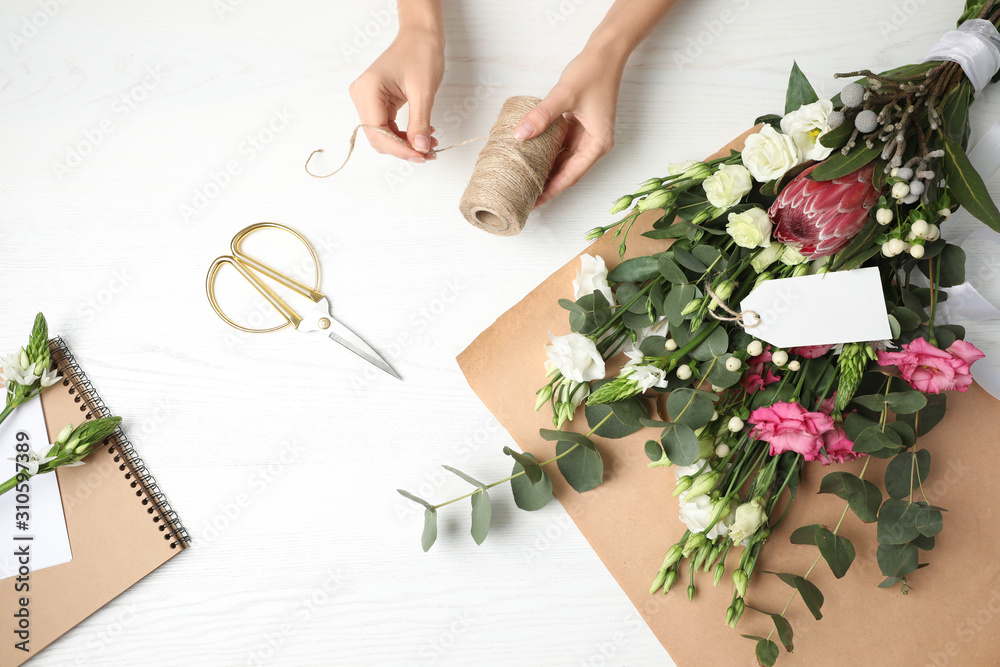 Fototapeta Florist making beautiful bouquet at white wooden table, top view