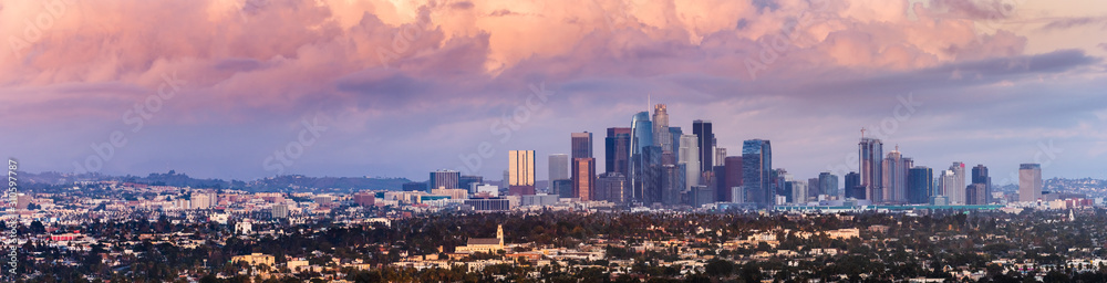 Fototapeta Panoramic view of downtown Los Angeles skyline at sunset, colorful storm clouds covering the sky; California