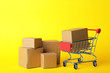 canvas print picture - Shopping cart and boxes on yellow background. Logistics and wholesale concept