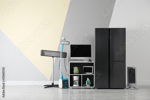 Modern refrigerator and other household appliances near color wall indoors Wallpaper Mural