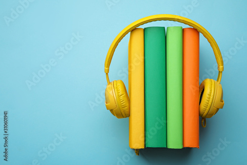 Books and modern headphones on light blue background, top view Canvas Print