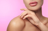 Woman with matte lipstick on pink background, closeup