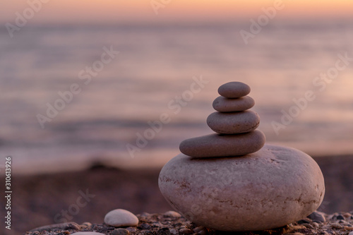 Perfect balance of stack of pebbles at seaside towards sunset Fototapet