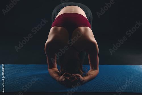 Fotografía  Young woman doing yoga in black studio, sirsasana headstand preparation