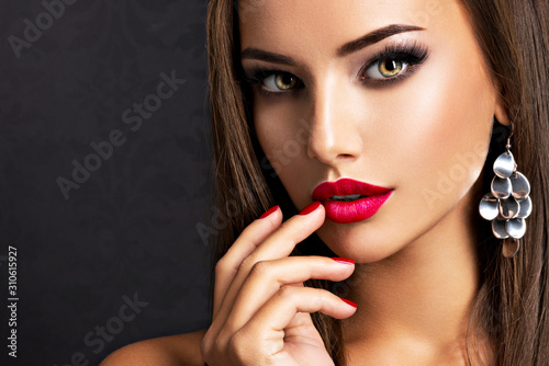 Photo seductive woman with dark brown eye makeup and bright red lips and nails