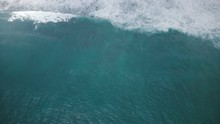 Drone Descending And Zooming In On Sea Water Surface And Giant Mint Blue Rushing Sea Wave Crashing Down With Foam