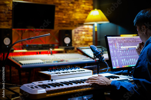 Photo professional male music producer arranging a song on computer in recording studio