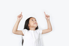 Portrait Of Asian Little Child Girl Pointing Two Forefinger Up And Looking Above Isolated Over White Background.