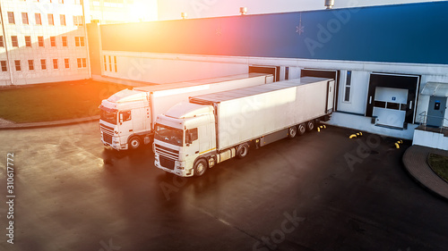 trucks are loaded in a modern logistics center.. Wallpaper Mural