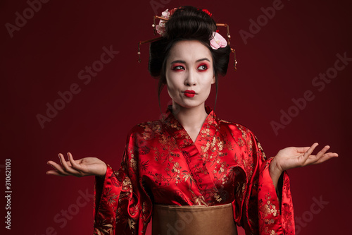 Fotografia, Obraz Image of beautiful young geisha woman in traditional japanese kimono hesitating