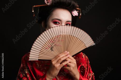 Valokuvatapetti Image of young geisha woman in japanese kimono holding wooden hand fan