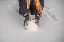 Young Woman Rolling Giant Snow...