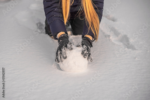 Fotografie, Obraz Young woman rolling giant snowball to make snowman
