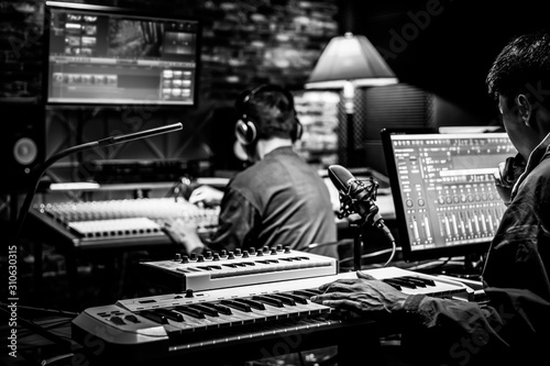 professional male producer, director, editor, composer working with sound engineer in recording studio. music production concept - 310630315