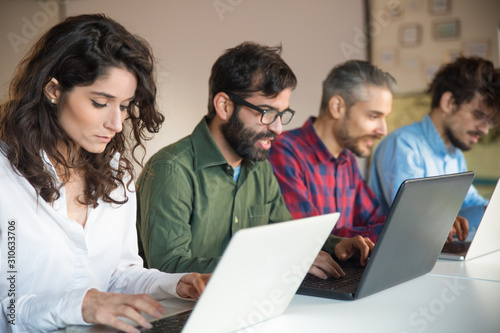Focused coworkers using laptops at meeting table. Business colleagues in casual working together in contemporary office space. Communication concept