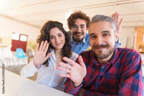 Fototapeta Portrait of happy successful creative team waving hello