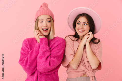 Image of young women in girlish clothes smiling and looking at each other Wallpaper Mural