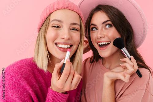 Photo Image of two joyful women smiling and applying makeup with cosmetics