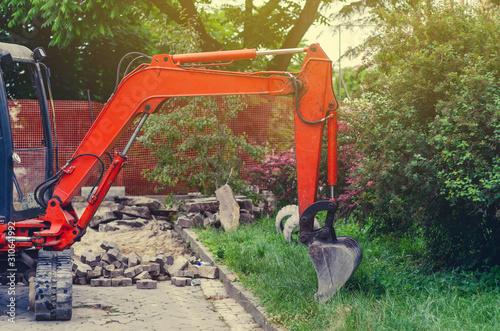 Canvastavla Small excavator on sidewalk near lawn. Repair in city, urban