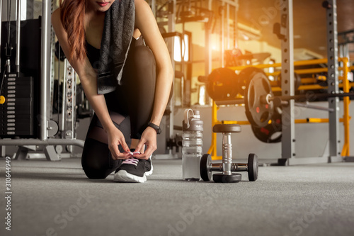 Fitness woman tying shoelaces before exercise workout at gym Tableau sur Toile