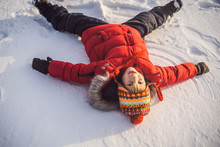 A Child, A Boy, Lies On The Snow, Makes A Snow Angel With His Arms And Legs, Emotions, Laughs