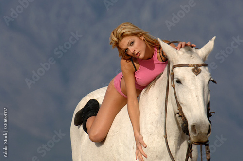 Beautiful young blonde girl on a horse at the landscape Canvas Print