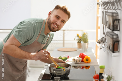 Fototapeta Young man cooking delicious soup in kitchen obraz