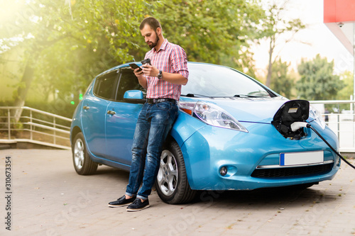 Платно Young handsome man use phone and drink coffee while his electro car charging at station