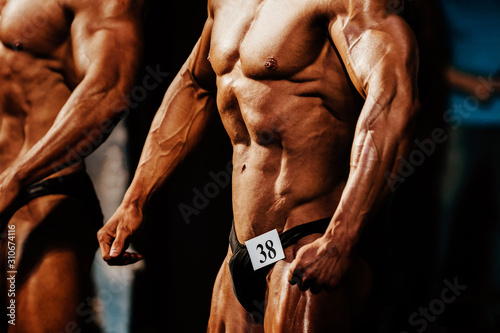 Obraz athlete man bodybuilder posing chest muscles and abs bodybuilding competition - fototapety do salonu