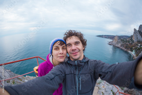 Photo  Loving couple takes a selfie on top of a cliff.
