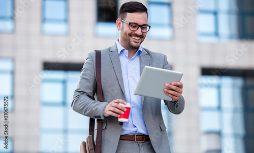Carta da parati  Businessman drinking coffee and checking notes with tablet
