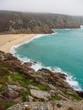 Wide vertical view of a sandy bay beach along the coastal granite cliffs of Porthcurno. Conrwall, United Kingdom. Travel and tourism.