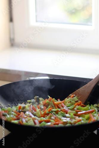 Carrot, leek and pumpkin, stir frying in a wok. Selective focus. Wallpaper Mural