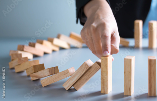 Tela  businessman hand stop dominoes continuous toppled or risk with copyspace