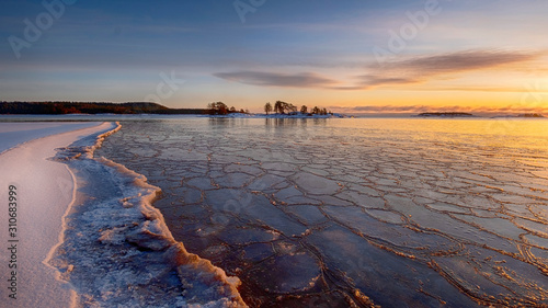 Valokuvatapetti The first ice  off the coast on the water in Lake Ladoga at dawn with fresh snow