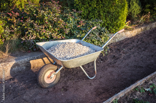 Fotomural  Single wheel garden wheelbarrow loaded with crushed stone prepared for garden pa