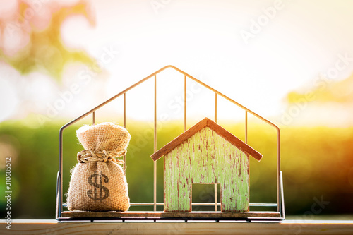 Fototapeta Money bag and house model put in the shelf with shape home on grass on sunlight in the public park, for Business investment loan or for save money for buy a new real estate concept. obraz