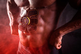 Bodybuilder male African uses electronic belt muscle stimulator trainer abdominal muscles on a black background with red smoke