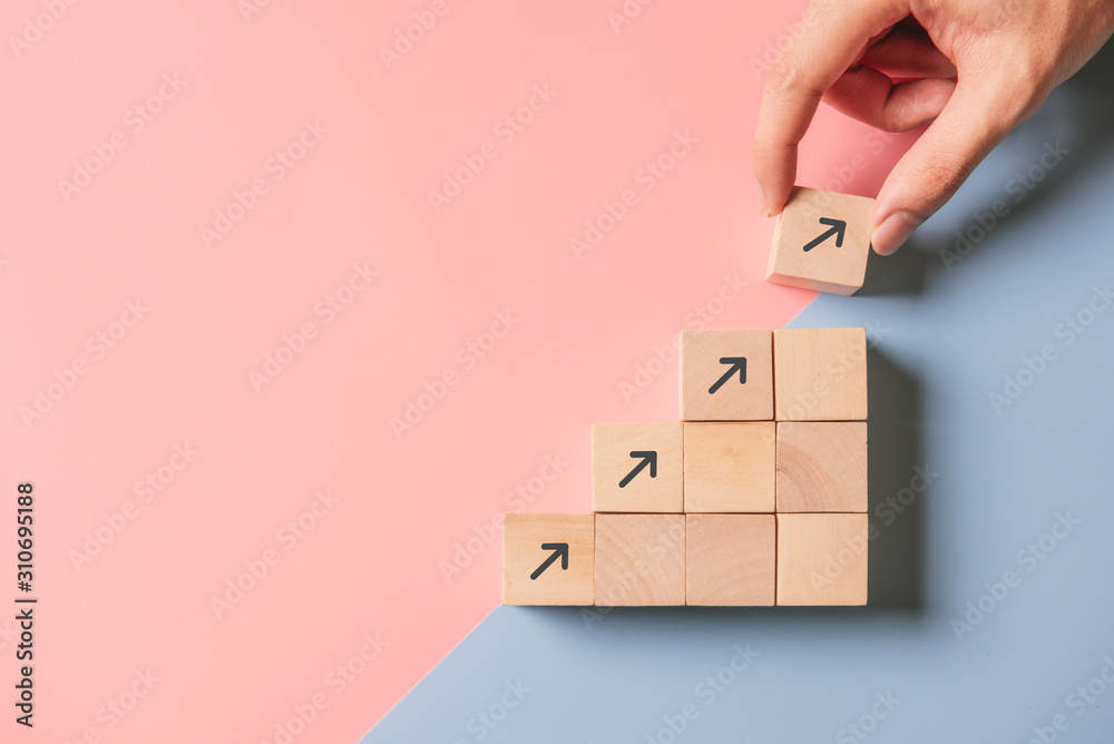 Fototapeta Business concept growth success process, Close up man hand arranging wood block stacking as step stair on paper blue and pink background, copy space.