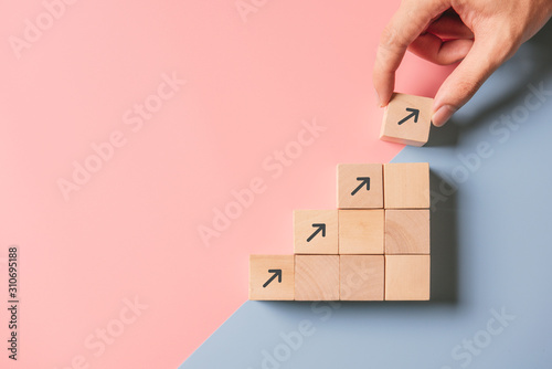 Fotografia Business concept growth success process, Close up man hand arranging wood block stacking as step stair on paper blue and pink background, copy space