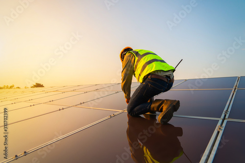 Obraz Portrait of engineer man or worker, people, with solar panels or solar cells on the roof in farm. Power plant with green field, renewable energy source in Thailand. Eco technology for electric power. - fototapety do salonu