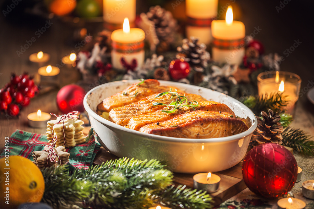 Fototapeta Christmas dinner from fish salmon in roasting dish with festive decoration advent wreath and candles.