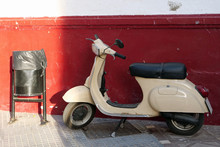 Old Cream Colored Vespa / Motor Scooter Next To Rubbish Bin In Front Of Red Wall