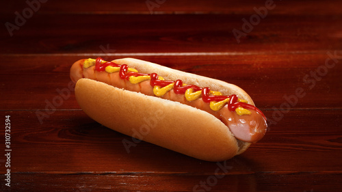 Obraz na płótnie Classic hot dog with ketchup and mustard on a background of wooden boards